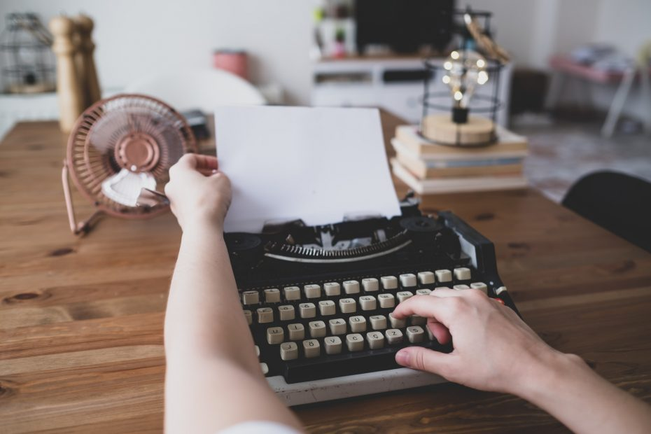writes book with old typewriter on wooden table. vintage fan and bulb decor. retro decor home.